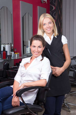 young beautiful woman and her hairdresser at barbershop photo