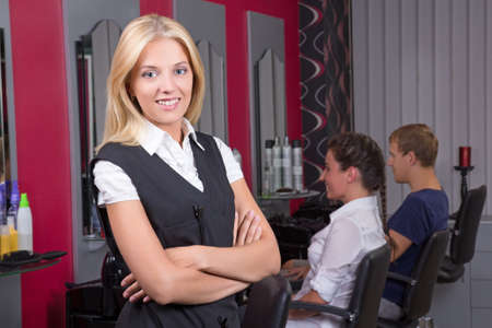 portrait of young professional hairdresser posing in beauty salon