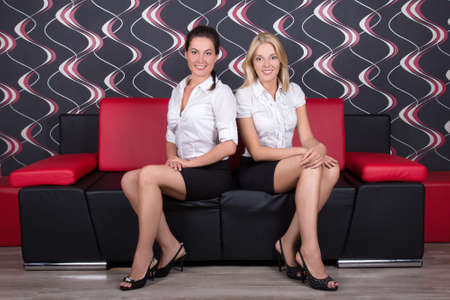 young beautiful brunette and blond sitting on the sofa photo