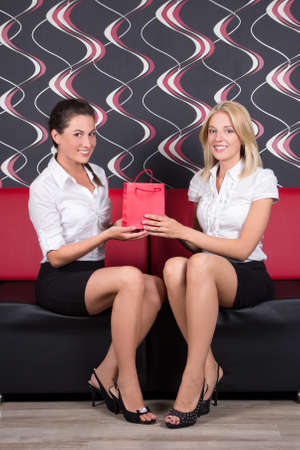 beautiful brunette and blond sitting on the sofa with gift bag photo