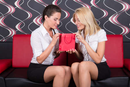 red sofa: two girls sitting on red sofa with gift