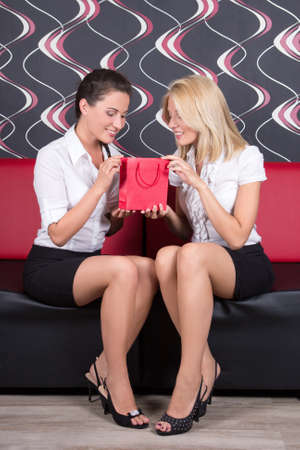 two pretty girls sitting on red sofa with gift photo