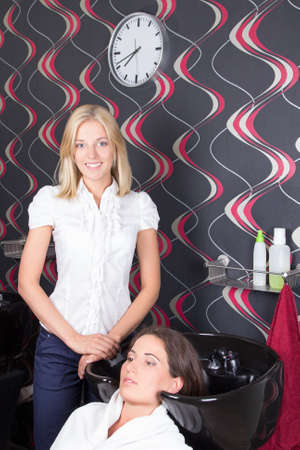 young hairdresser washing customers hair at a beauty salon photo