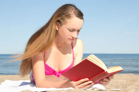 young attractive woman in pink bikini reading book on the beach photo