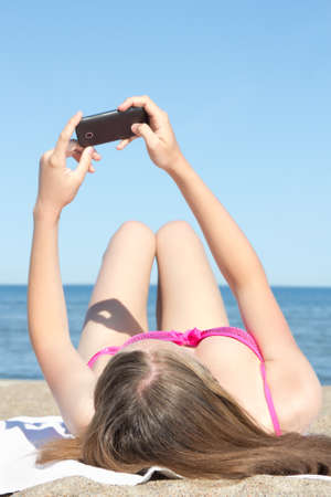 young woman photographing herself with mobile phone on the beach photo