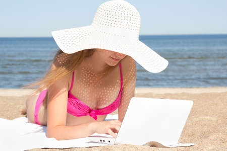 young beautiful woman working on her laptop at the beach photo