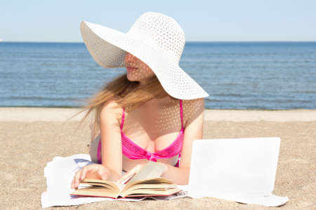 beautiful female student with white laptop and book on the beach photo