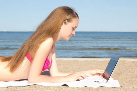 beautiful teenage girl working on white laptop at the beach photo