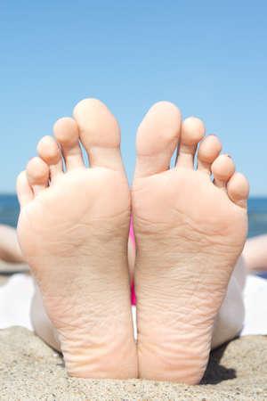 female heels on the sandy beach near the sea photo