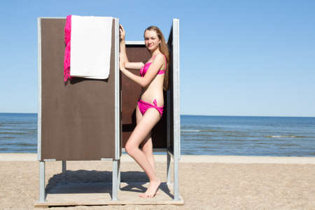 young beautiful woman in dressing cabin on the beach photo