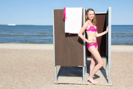 young slim beautiful woman in changing cabin on the beach photo