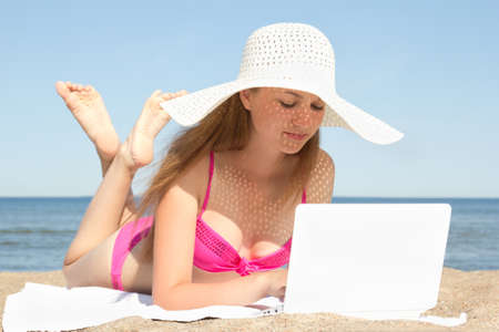 young beautiful woman working on her white laptop at the beach photo