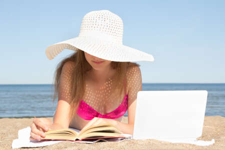 young woman with white laptop and book on the summer beach photo