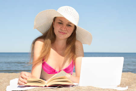 beautiful female student with laptop and book on the beach photo