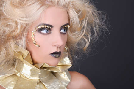 young mysterious woman with blondie shaggy hair and creative makeup photo