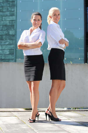 two young attractive business women posing outside photo