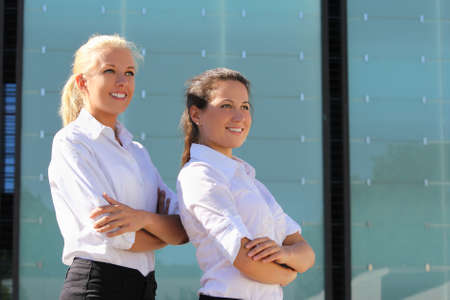 portrait of two young attractive business women posing outside photo