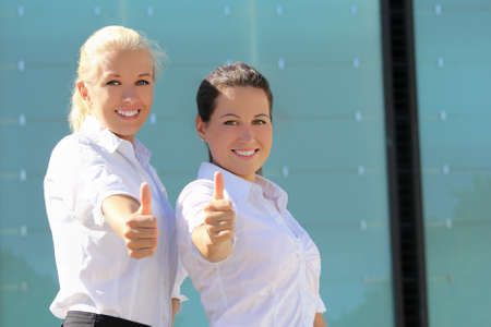 portrait of two young attractive business women with thumb up photo