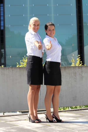 two young attractive business women with thumb up photo