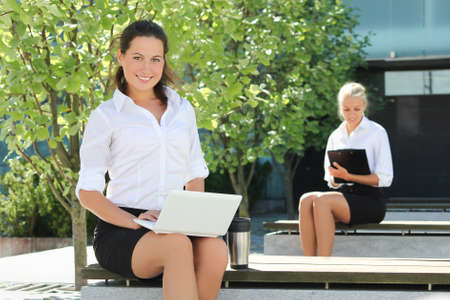 young attractive business women with folder and laptop sitting outside photo