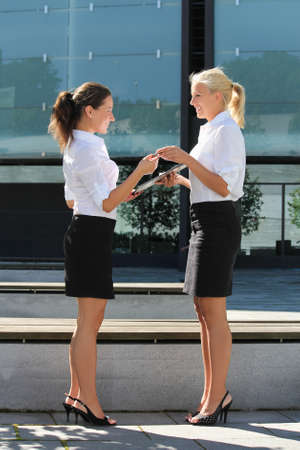 two attractive business women signing contract outside photo