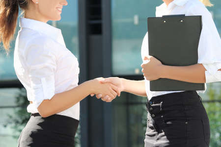 sexy business women: two sexy business women shaking hands in street Stock Photo