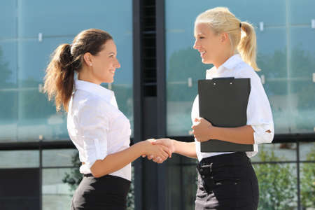 two young beautiful business women shaking hands in street