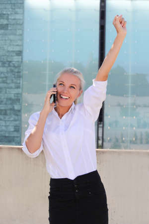 attractive successful business woman calling on the phone outside photo