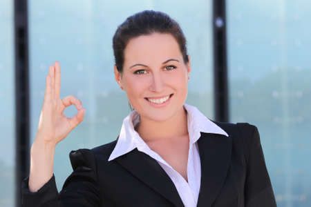 young business woman in black suit showing ok outside photo