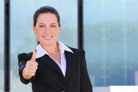 young business woman in black suit thumbs up outside photo