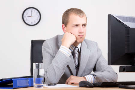 young bored businessman sitting in his office photo
