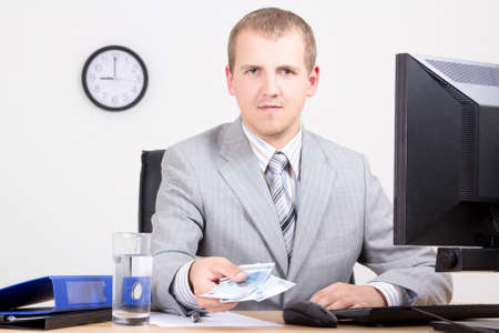 young business man giving money in bright office Stock Photo