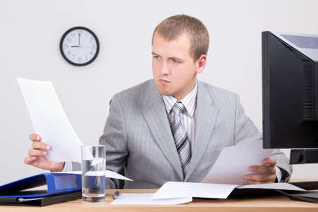 young worried accountant doing paperwork in office photo