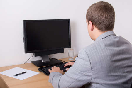 business man using personal computer in bright office Фото со стока