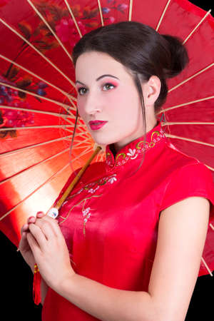 portrait of young beautiful woman in red japanese dress with umbrella photo