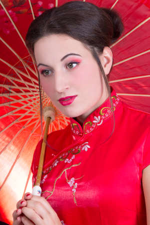 close up portrait of young beautiful woman in red japanese dress with umbrella photo