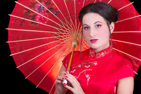 close up portrait of beautiful geisha in red japanese dress with umbrella photo