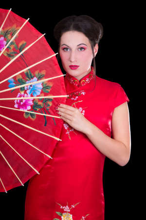 portrait of young beautiful geisha in red japanese dress with fan photo