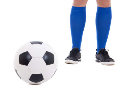 legs of soccer player in blue gaiters with ball isolated on white background photo