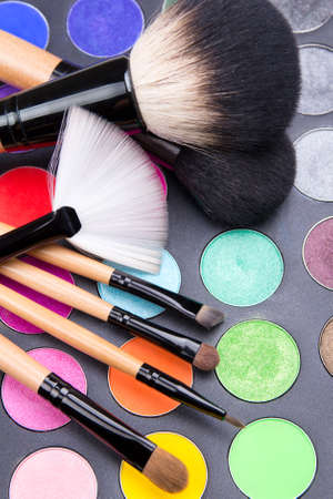 close up of make-up brushes and colorful eyeshadow palette over black background