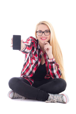 young happy blondie woman sitting and showing mobile phone in her hand isolated on white background