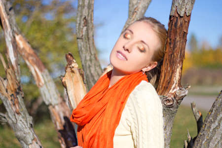 young dreaming woman and dried tree in autumn park photo