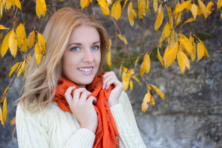 portrait of attractive woman in white woolen sweater smiling against stone wall photo