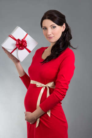 portrait of young beautiful pregnant woman in red dress with gift box over grey background Stock Photo - 23042702