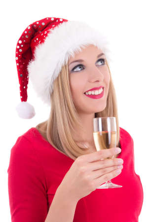 beautiful young woman in santa hat dreaming with glass of champagne isolated on white background photo