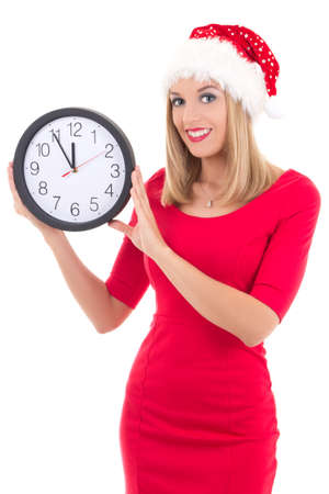 young woman in santa hat with clock posing isolated on white background photo
