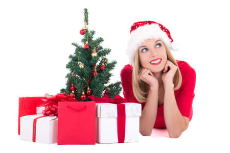 Dreaming woman lying down with christmas tree and gifts isolated on white background photo