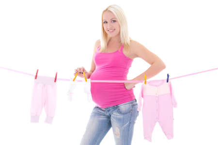 happy pregnant woman hanging out child clothes isolated on white background photo