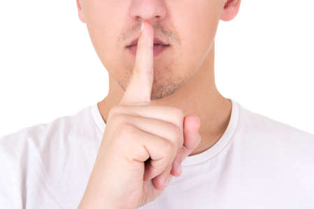 hushed: close up of man with finger on lips asking for silence isolated on  white background Stock Photo