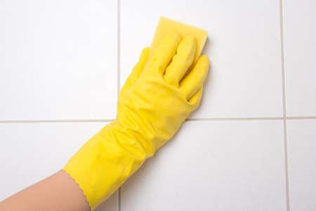 empleadas domesticas: Mano de limpieza guante amarillo azulejo Foto de archivo